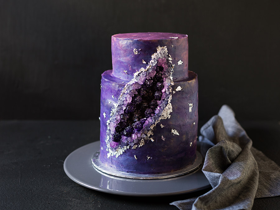 Purple Geode Cake frosted to look like a galaxy with a carved indent filled with purple and pink rock candy and silver leaf edging